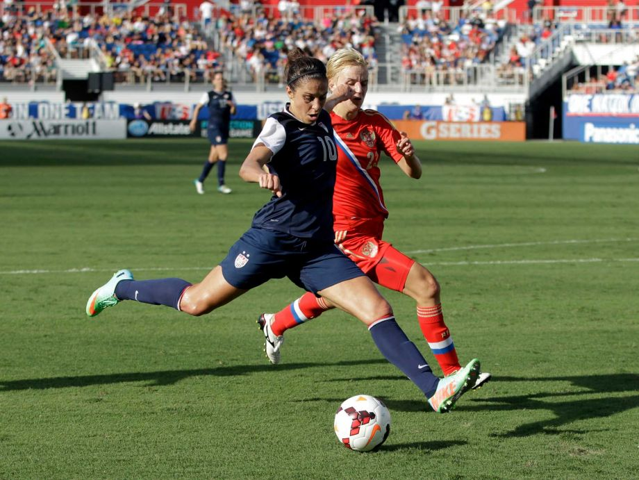 Carli Lloyd, left, of the United States beats Elena Morozova to score one of her two goals in the Amercans' 7-0 victory versus Russia in 2014